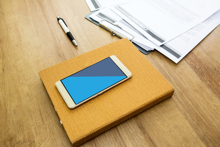Working table with notepad, pen, document and smartphone. Wooden table background. Office background. Stock fotó