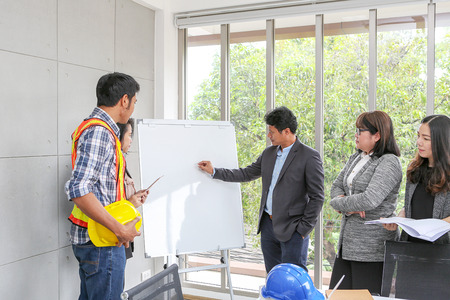 Executives are explaining plans on a whiteboard. Confident boss explaining something to employee. Planning of engineers and technicians. Engineers and Architects Planning for a project. Asian people.