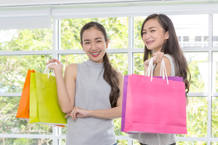 Two women happy with shopping bags on hand. Shopping Lady smiling. Beautiful Asian girl. young shopper. Stockfoto