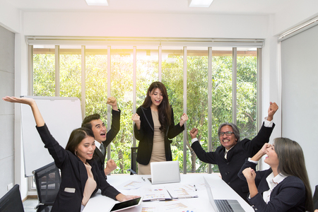 Group of happy business people cheering in office. Celebrate success. Business team celebrate a good job in the office. Asian people. Imagens