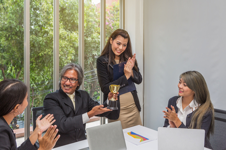Business team winning trophy in the office . Businessman with teamwork in award and successful showing trophy and rewarded for in the office. asian people. Meeting at the office.