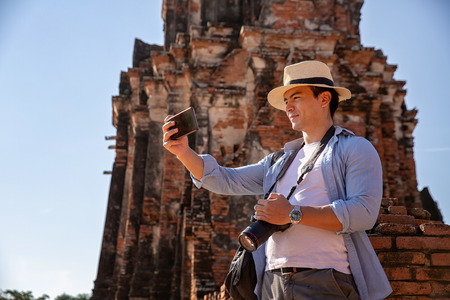 Tourists are shooting self portrait. Selfie portrait. Travel and tourism. Young caucasian male walk in the morning at temple in old city of Ayutthaya in Thailand.