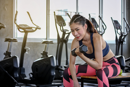 Concept fitness sport training lifestyle. Girl lifting dumbbells. Active sport athletic woman with dumbbells pumping up muscles body.