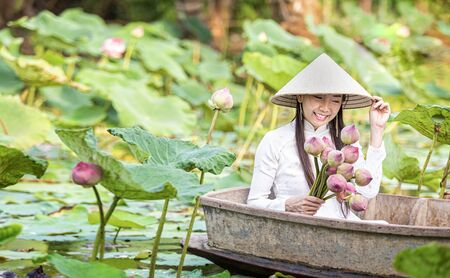 A Vietnamese woman is sitting on a wooden boat and collecting pink lotus flowers. Female boating on lakes harvest water lilies. The flooding season there are many water lilies on the lakes.