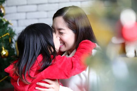 Holidays and people concept. Mother and child are celebrating Christmas. Happy mother and daughter decorating christmas tree. Mom and child are kissing each other.