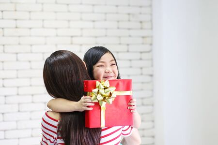 Merry Christmas and Happy Holidays or Happy New year. Mom gives gifts to children. Cute girl gives his beloved mother a gift. New year's decorate in the living room. Stock Photo