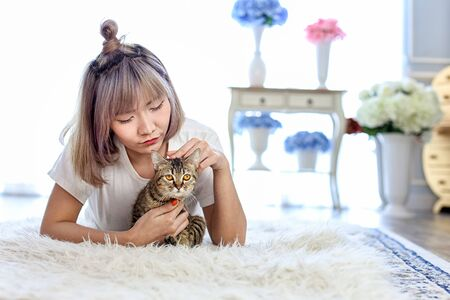 Thai cat in the embrace of the woman lying on the wool carpet. Young Female lying in bed and holding her beautiful cat. Beautiful young woman with cute cat lying in wool carpet at home.