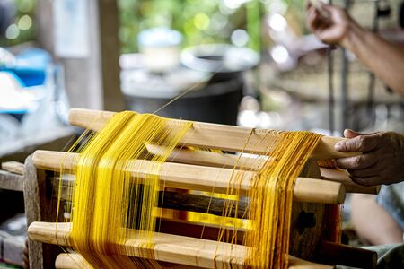 Crafts and craftsmanship. Silk raising for silk threads. yarn warping machine in a textile weaving craftsmanship. Hand of woman weaving and spinning natural colorful threads or yarn.