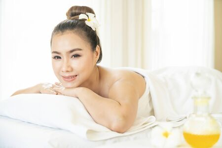 Beautiful woman in spa. The young woman is waiting to sit in the spa on the window. Asian woman in wellness beauty spa having aroma therapy massage with essential oil. Thailand. Selective Focus.