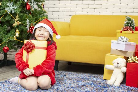 X-mas and holiday concept. A little girl wearing a Christmas costume hugs the gift in the living room. Happy childen girl in christmas cap hands present wrapped with gold paper and red ribbon.