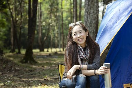 Girl drinking hot water in camping. Beautiful young woman with a tent of outdoor. Asian woman camping and backpack travel sitting relax alone in forest. A young female relaxing in front of a tent.
