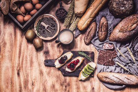 Breakfast and baked bread concept. Fresh fragrant bread and egg on wooden table. Fresh bread and coffee and wheat on wood black background. Kiwi and chocolate and Sesame seeds.