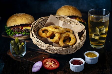 Fresh and juicy hamburger. Cheese burger with beef or bacon, patty tomato, onion ring and sparkling water or beer. Junk food to eat. gorgonzola on table.