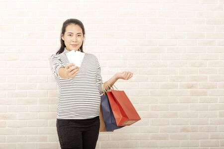 Pregnant women, credit and shopping bags. Young pregnant woman over brick wall background holding shopping bags and credit card.