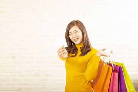 Beautiful asian girl carrying shopping bags. Shopping woman smiling. Beautiful Asian girl. young shopper on brick background.