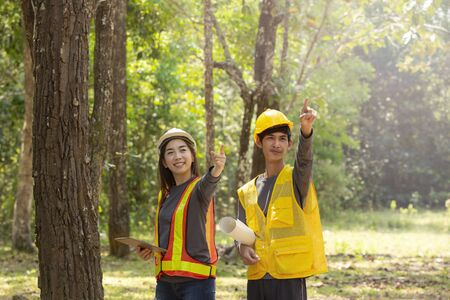 The supervisors are constructing roads in the forest. Young Engineer female holding blueprint on hand. Engineer team working on project at the forest. Technical operaters and Labourers.