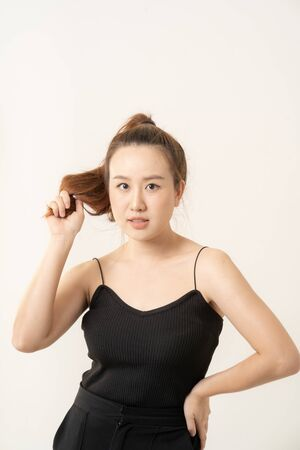 Woman holding hair on a white background. Attractive young woman over white background.