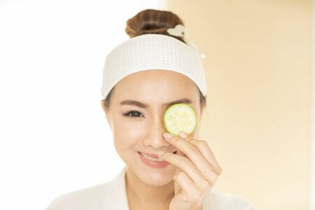 Beauty and spa condo, woman holding cucumber. Young woman with facial mask holding cucumber slices on white background. Stockfoto
