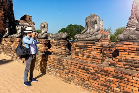 Young Male photographing Buddha images in Old Town, Ayutthaya Province. ravel and tourism. Young caucasian man walk in the morning at temple in old city of Ayutthaya in Thailand.