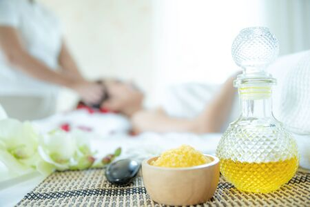 Bottle of oil and spa salt With the background as Beautiful woman taking a spa facial. Beautiful female taking facial massage treatment in the spa salon.