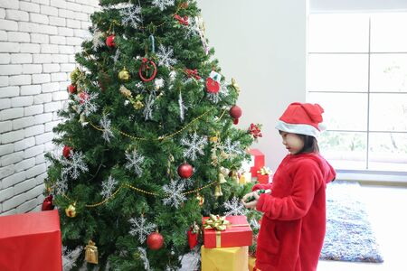 Asian girls wearing red dresses are decorating Christmas trees. Children decorate presents on Xmas eve. Merry Christmas and Happy new year.