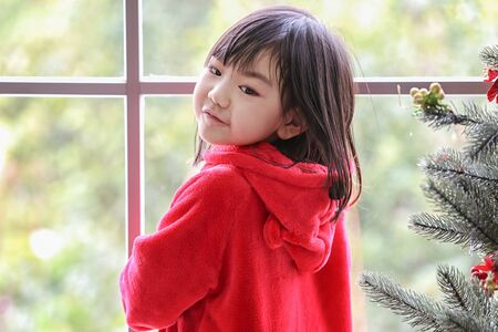 A girl in a red suit standing by the window. Girl stands near window looking aside. child alone in home.