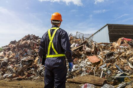 Engineer and recycle. Engineers standing in recycling center. back view of Male foreman wearing protective equipments and holding tablet and looking at  Recyclable material.