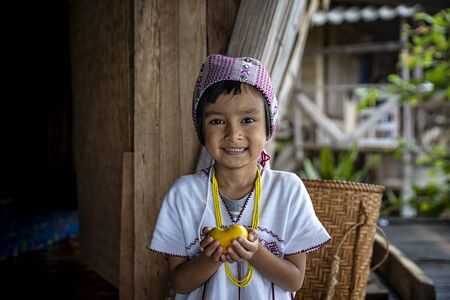 Pga Ka nyau (Pakhayo) Tribe Children Show the persimmon in her house. Ban Pa Bong Piang Northern region in Mae Chaem District Chiangmai Province That has the most beautiful rice terraces in Thailand.