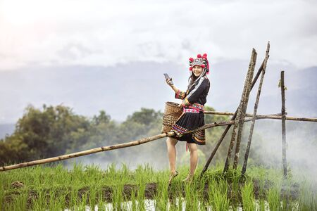 Hmong girl using mobile phone in rice terraces. Ban Pa Bong Piang Northern region in Mae Chaem District Chiangmai Province That has the most beautiful rice terraces in Thailand.
