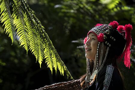 Hmong girl her have tooth braces and standing in the forest with a beautiful light in the morning in the spring. Portrait of beautiful asian lady Akha tribe or Hmong tribe in Chiang mai, Thailand. Stockfoto