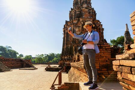 A man taking a selfie with a mobile phone in Ayutthayas old town. Young caucasian happy smiling tourist man taking selfie with mobile phone.