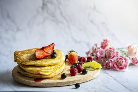 Delicious pancakes with fresh berries and honey on marble patterned floor with pink carnation and background.