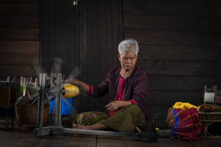 Craftsmen of Thai Silk. Local teachers is master are the original silk weaving in the community of Buriram province. Thai old woman shows weaving spinning natural colorful threads or yarn.