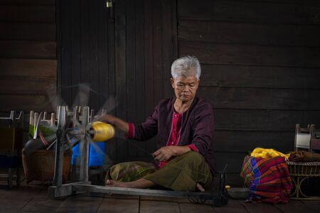 Handwerker aus thailändischer Seide. Lokale Lehrer sind Meister der ursprünglichen Seidenweberei in der Gemeinde Buriram. Die thailändische alte Frau zeigt das Spinnen von natürlichen bunten Fäden oder Garnen.