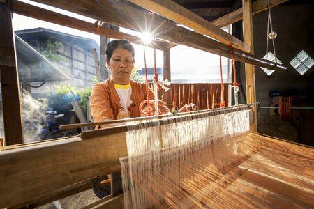 Traditional Isan Thai silk weaving. old woman hand weaving silk Akkanee in traditional way at manual loom. Phu fabric dyeing volcanic igneous or soil. Buriram, Thailand.