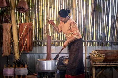 Craftsmen of Thai Silk. Older women dye silk with colors from volcanic soil. Phu fabric dyeing volcanic igneous or soil. Buriram, Thailand.