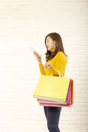 Young women using mobile phones to order products in online stores.