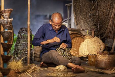 Craftsmen of Thai. An old man who is the craftsmanship in Buriram Province Weaving a basket of bamboo. Craftsmanship that has been carried on since ancient times. Stock Photo