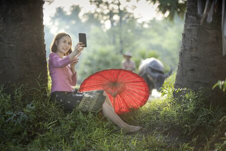 Life of Southeast Asian people. Young women taking selfie in the fields with the buffalo and her father. Female using a smartphone in a rice fields.