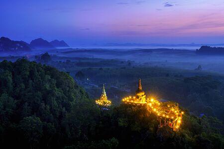 Khao Na Nai Luang Tham Park. Pagoda at sunrise on the top at Khao Na Nai Luang Dharma Park with fog. Beautiful Temple at Surat Thani province, Thailand.