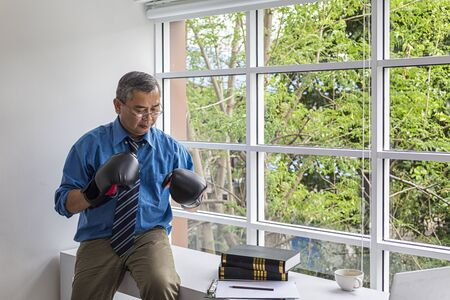 Business people wear boxing gloves Thinking about business planning. Businessman in boxing gloves at the office.