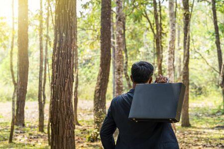 Business people are looking at forests to plan cities and buildings. Businessman in forest holding briefcase. Asian engineers work on plans construction in the forest park. Stock Photo
