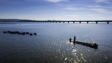 Fischer stellen Fischfallen im Lam Pao Dam auf, vor der Kulisse der Berge und der Thepsuda-Brücke. Provinz Bueng Kan.