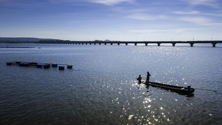Fishermen are placing fish traps in the Lam Pao Dam, with a backdrop of mountains and the Thepsuda Bridge. Bueng Kan Province.