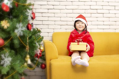 Christmas and holiday concept. Girl holds a gift box on Christmas day sit on sofa bed. Happy children girl with gift box. Girl in christmas cap hands present wrapped with gold paper and red ribbon.