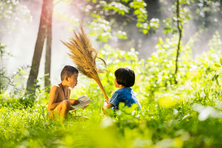 Asian students reading letter in a forest. The boys and girls are talking about the letters and exam results of the school in the countryside. Kids go back to school. Stockfoto