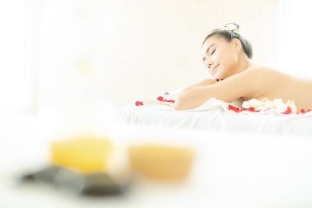 Natural cosmetics and concept. Close up of salt with massage oil and bath towel on Spa bed. Bottle of massage oil, hot stone spa and salt with woman massage in a beauty spa bed.
