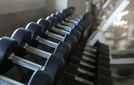 Motivation for Sport. Dumbbell sets in the gym. Sports equipment on a gymnasium background. Side view.  Selective focus.
