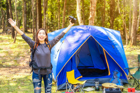 Asian woman holding binoculars And happy to travel in the forest.  Asian women camping and resting at forest happy on weekend. Stockfoto