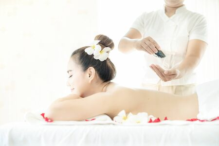 Beautiful female in spa. Spa oil massage for relaxation. Asian woman in wellness beauty spa having aroma therapy massage with essential oil. Thailand. Pour spa massage oil onto hands.